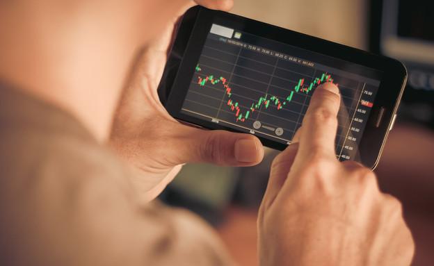 גבר בודק שערי מניות בסמארטפון (אילוסטרציה: Kidsada Manchinda, shutterstock)