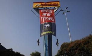 פעילי גרינפיס תולים את השלט (צילום: חוסין אל אוברה)