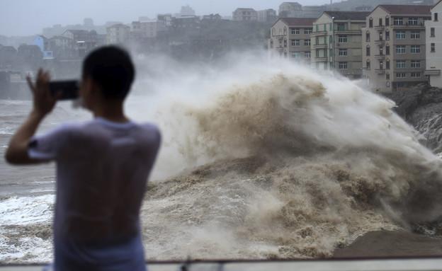 אדם מצלם את הגלים בעקבות טייפון לקימה בסין