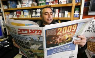 בעל קיוסק קורא עיתון, 2009 (צילום: מרים אלסטר, פלאש 90)