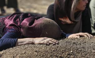 כורדית בסוריה על קברו של בן משפחתה (צילום: Sakchai Lalit | AP)