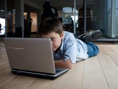ילד שוכב מול מחשב נייד