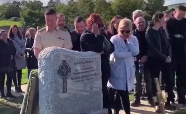 שר מתוך הקבר בלוויה (צילום: Irish Defence Forces Veterans News)