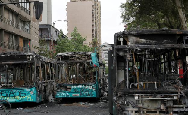 אוטובוסים שהוצתו במהלך ההפגנות בסנטיאגו (צילום: רויטרס)