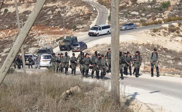 כוחות מג״ב והמנהל האזרחי נעים מיצהר לכיוון הגבעה הסמוכה (צילום: החדשות12)