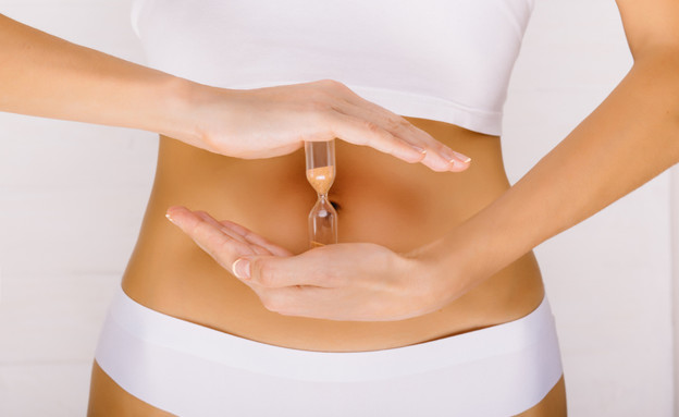 שעון חול מול בטן של אישה (אילוסטרציה: Erica Smit, shutterstock)