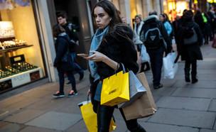 אישה עושה קניות ברחוב (צילום: getty images)