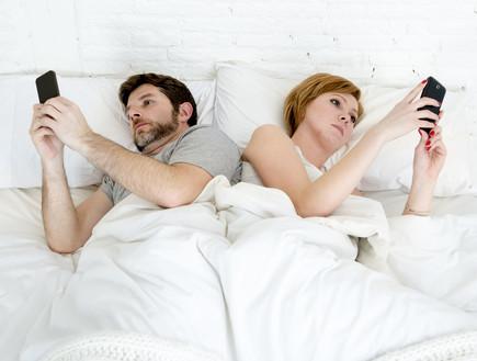 זוג עם פלאפונים במיטה