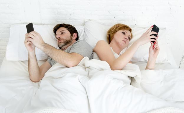 זוג עם פלאפונים במיטה (צילום: Shutterstock)