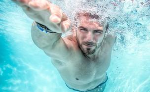 גבר שוחה בבריכה (צילום: shutterstock, Nadezda Barkova)