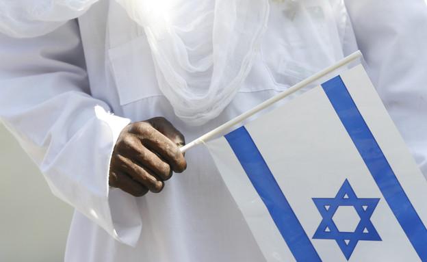 אדם אתיופי מחזיק את דגל ישראל (צילום: מיכל פתאל, פלאש 90)