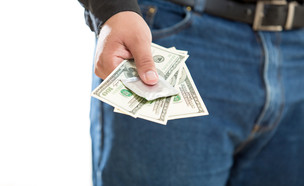 גבר מושיט יד עם כסף (צילום: ShutterStock)
