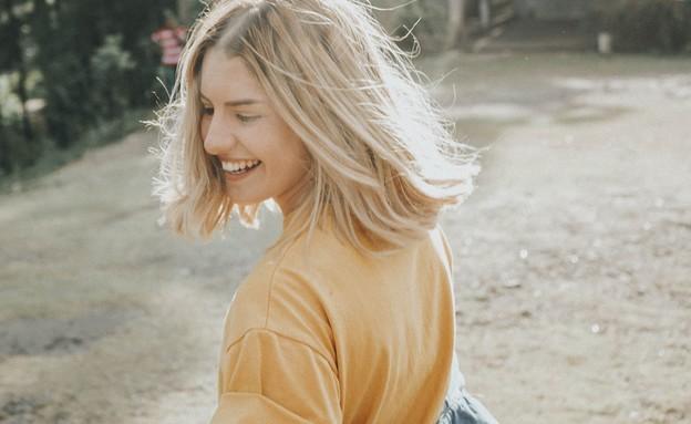 אישה שמחה (צילום: gian-cescon-unsplash)