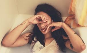 אישה שוכבת באמבטיה עם בגדים (אילוסטרציה: naomi august, unsplash)