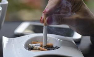 אישה מכבה סיגריה (צילום: buenaventura, shutterstock)