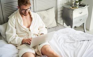 גבר במיטה עם מחשב (צילום: Olena Yakobchuk, shutterstock)