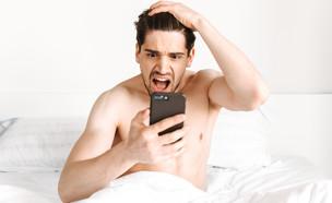גבר במיטה עם טלפון (צילום: Dean Drobot, shutterstock)