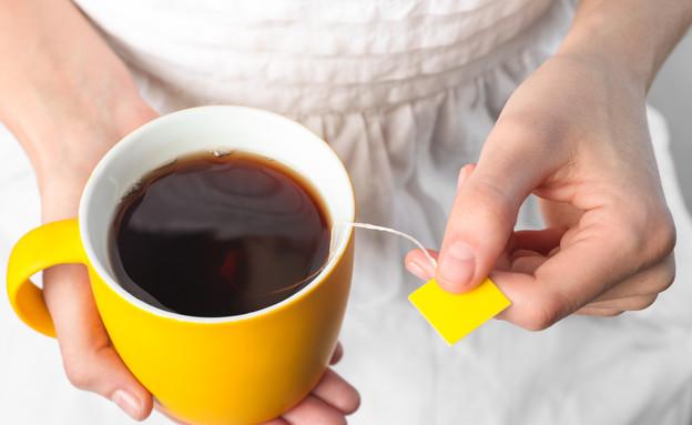 אישה מחזיקה כוס תה (צילום: New Africa / Shutterstock.com)