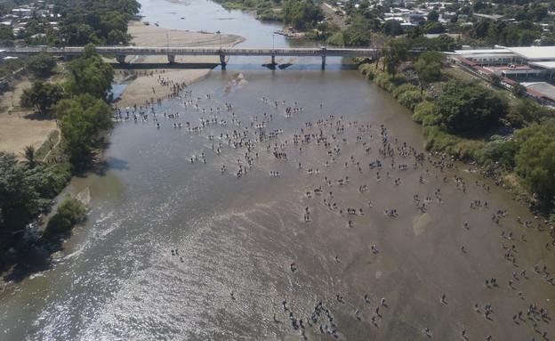 מאות המהגרים שחוצים את הנהר בגואטמלה, לעבר מקסיקו (צילום: AP)
