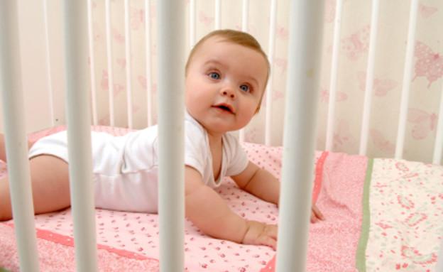תינוקת עירנית בעריסה (צילום: LisaValder, Istock)