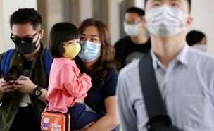 אישה לובשת מסכה בסין (צילום: רויטרס)