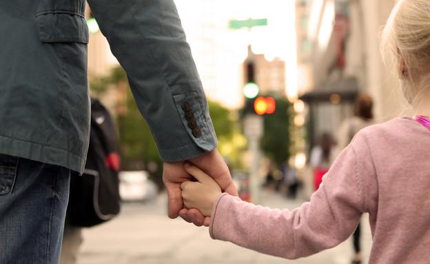 גבר מחזיק יד של ילדה