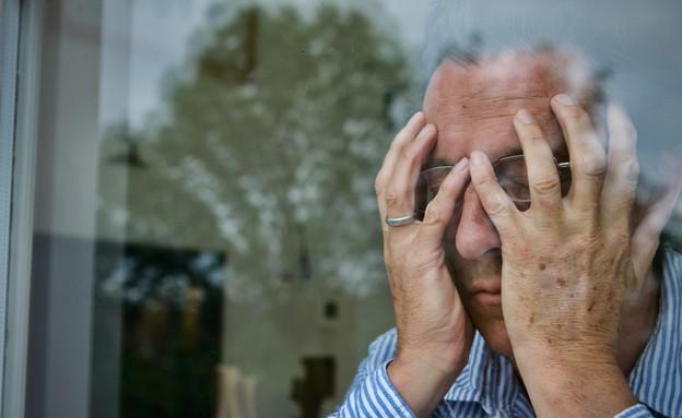 גבר מבוגר מחזיק את הראש בין הידיים (אילוסטרציה: J K Daylight, shutterstock)
