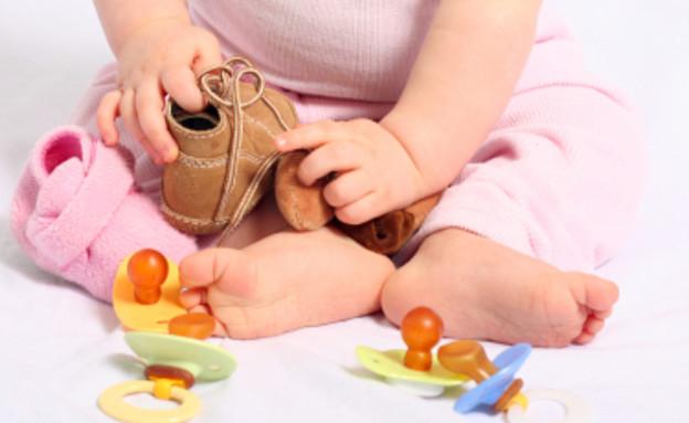 תינוק מחזיק נעליים ולידו מוצצים (צילום: istockphoto)