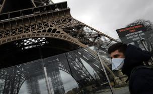 גבר במסכה ליד מגדל אייפל בפריז הסגור בשל הקורונה ( (צילום: Christophe Ena, getty images)