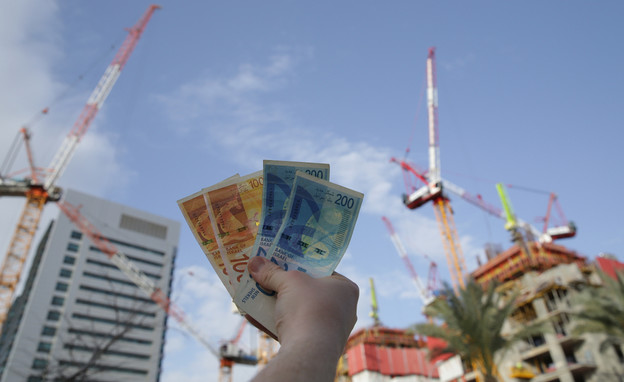 יד מחזיקה שטרות מול אתר בנייה (אילוסטרציה: Irina Tarzian, shutterstock)