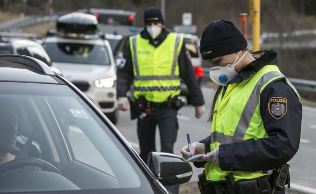 שוטרת בודקת אישורי מעבר בסגר באוסטריה  (צילום: Jan Hetfleisch, getty images)