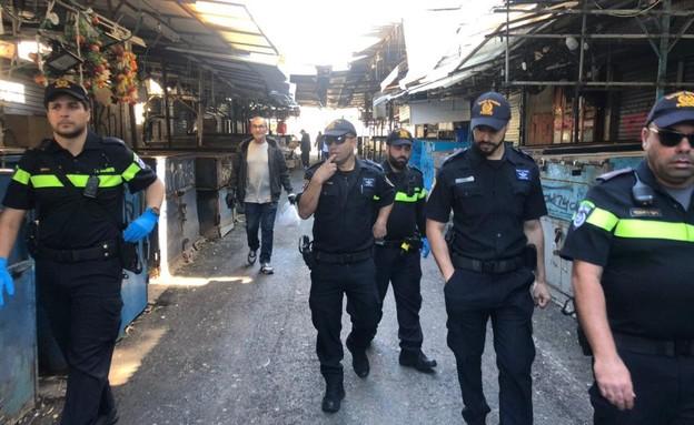 שוטרים סוגרים בסטות בשוק הכרמל (צילום: החדשות 12)
