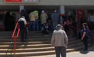 מצטופפים ליד סניף דואר ישראל בבאר שבע (צילום: שמעון איפרגן)