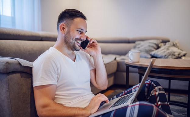 גבר עובד במחשב לבוש בפיג'מה