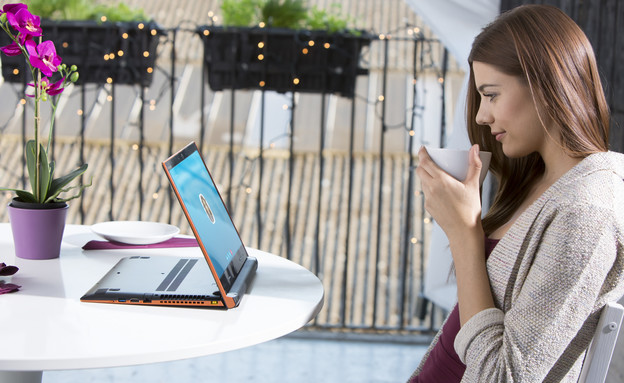 אישה יושבת במרפסת על קפה ולפטופ (צילום: Lenovo)