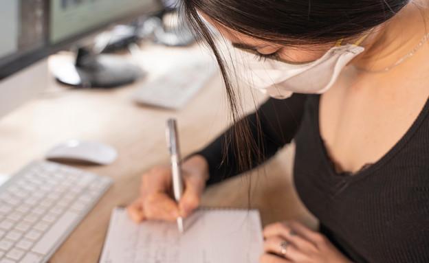 אישה עובדת במשרד עם מסיכה