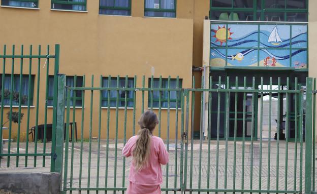 ילדה מסתכלת על שער בית ספר סגור בחדרה