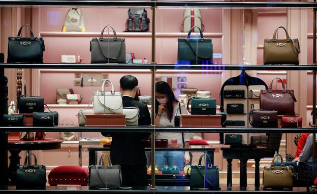 אישה קונה בחנות יוקרה בסיאול, דרום קוריאה (צילום: reuters)