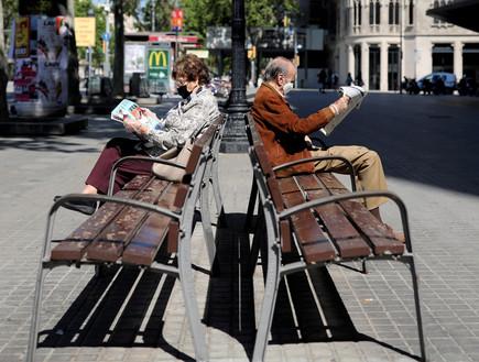 זוג מבוגרים קוראים עיתון עם מסיכות הגנה, ברצלונה (צילום: reuters)