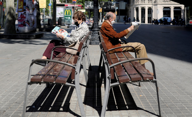 זוג מבוגרים קוראים עיתון עם מסיכות הגנה, ברצלונה