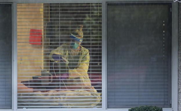 אחות מטפלת בחולה קורונה בוושינגטון (צילום: ap)