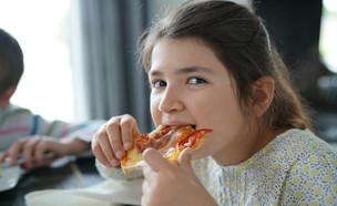 ילדה אוכלת פיצה (צילום: shutterstock_goodluz)