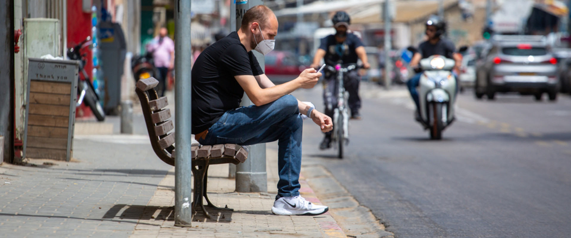 אדם לובש מסיכת פנים על ספסל ומסתכל בסמארטפון בתל אביב (צילום: S. Edelweiss, shutterstock)