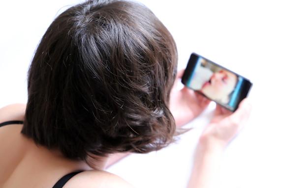 אישה צופה בטלפון (צילום: shutterstock | Oleg Elkov)