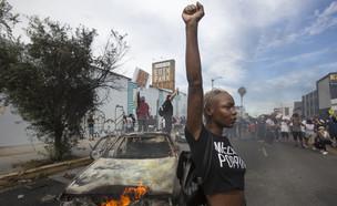 מפגינה על רקע מכונית שרופה במהומות בלוס אנג'לס (צילום: AP)