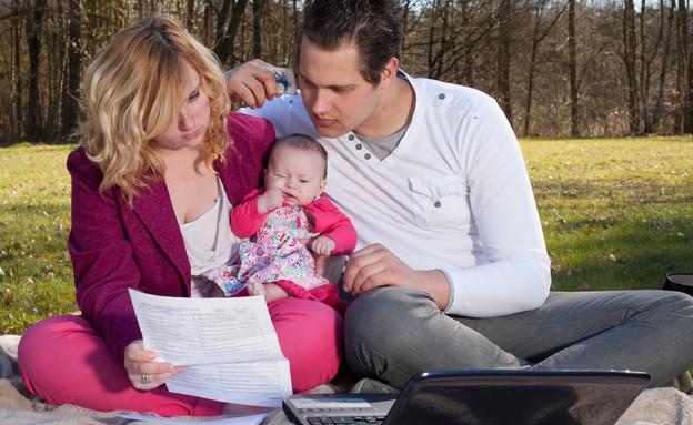 משפחה צעירה עם תינוק מסתכלת על קבלות (אילוסטרציה: DNF Style, shutterstock)