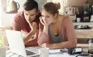 זוג עובר על הוצאות  (צילום: shutterstock  WAYHOME studio)