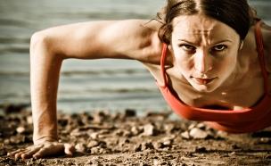 אישה עושה שכיבות סמיכה על החוף (אילוסטרציה: shutterstock)
