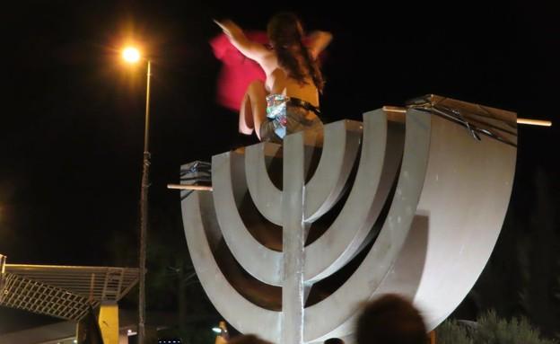 מפגינה על סמל המנורה (צילום: אם תרצו)