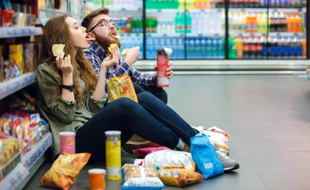 בחור ובחורה אוכלים ג'אנק פוד בסופר (צילום: Dean Drobot, Shutterstok, shutterstock)